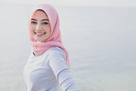해변에서 hijab 착용하는 아시아 여자의 아름 다운 미소의 초상화를 닫습니다