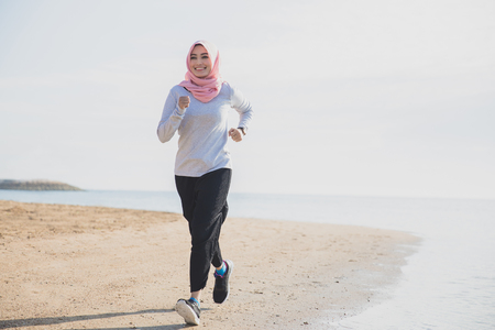 full body portrait of sporty woman wearing hijab smiling while jogging at the beach