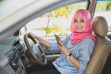 close up portrait of beautiful woman wearing hijab holding a smartphone while driving a car