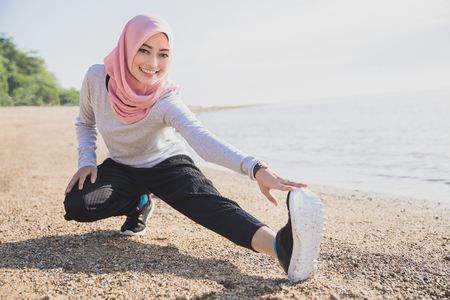 portrait of asian sporty woman wearing hijab smiling while doing leg stretching at the beach Stok Fotoğraf