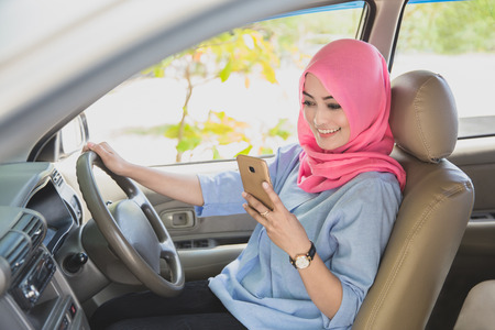 close up portrait of beautiful woman wearing hijab texting on smartphone while driving a car Stock Photo