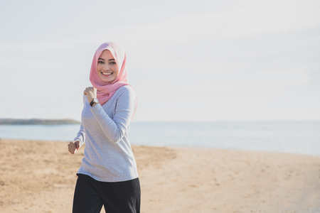 portrait of sporty woman wearing hijab smiling while jogging at the beach with copy space