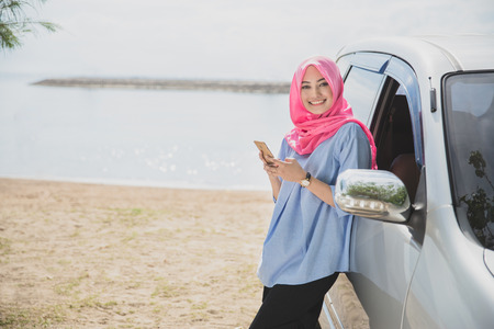 portrait of beautiful asian woman smiling while holding mobile phone lean back on her car with beach on the background