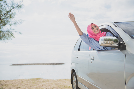 portrait of beautiful woman wearing hijab waving her hands while driving a car with beach on the background Фото со стока