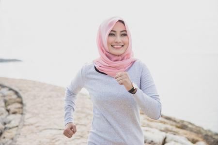 조깅 트랙에서 hijab 조깅을 입고 아시아 스포티 한 여자의 초상화를 닫습니다 스톡 콘텐츠