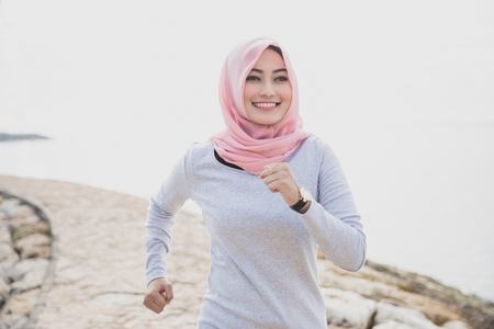 close up portrait of asian sporty woman wearing hijab jogging at the jogging track Stok Fotoğraf - 80019365
