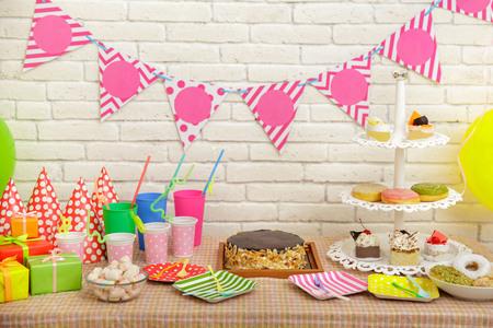 Portret van tafel opgericht voor het feest van het kind met witte bakstenen muur op de achtergrond Stockfoto