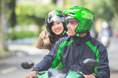 happy passenger directing commercial motorcycle taxi driver to go to her destination