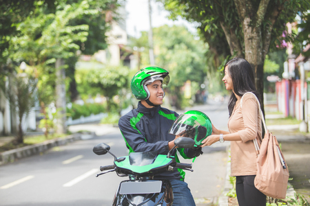 portrait of happy commercial motorcycle taxi driver giving helmet to his customer