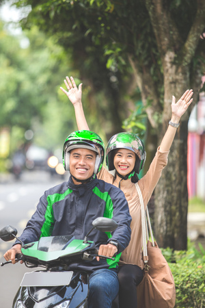 Happy excited commercial motorcycle taxi driver taking cheerful passenger to her destination Stock Photo