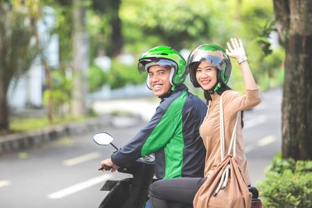 Gelukkige passagier die vaarwel golven terwijl het zitten op een commerciële motorfietstaxi