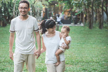 parent with their cute baby walking together in the park