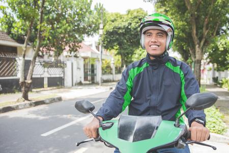 상업 오토바이 드라이버로 행복 한 아시아 사람이 작동의 초상화