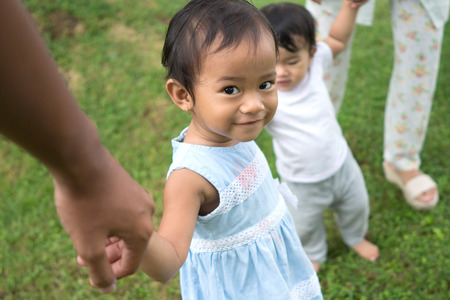 portrait of a baby girl walking in park with her parent