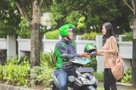 Portret van gelukkige commerciële motorrijders taxichauffeur die helm geeft aan zijn klant Stockfoto - 80162975