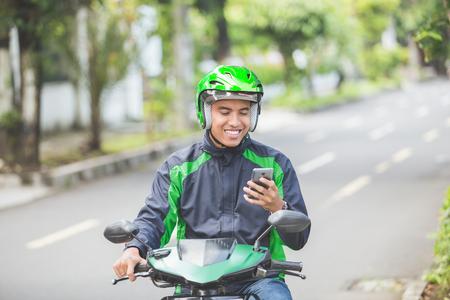 Retrato de hombre asiático feliz trabajando como un motorista de motorcyle comercial tomar el orden de su teléfono inteligente Foto de archivo - 80162976