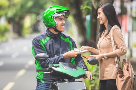 バイク タクシーの運転手に彼女の乗車のための幸せな顧客の肖像画を支払う 写真素材