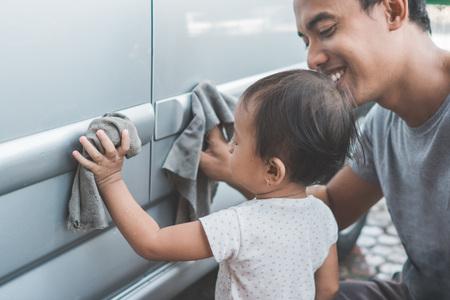 Portret van gelukkig kind is een beetje helper door haar papa te helpen om de auto te reinigen Stockfoto