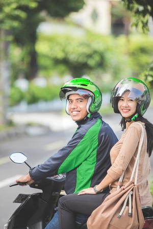 Gelukkige commerciele motorrijderschauffeur die zijn passagier naar haar bestemming neemt