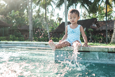 kid enjoying summer by sitting on a side pool playing with water Stock Photo