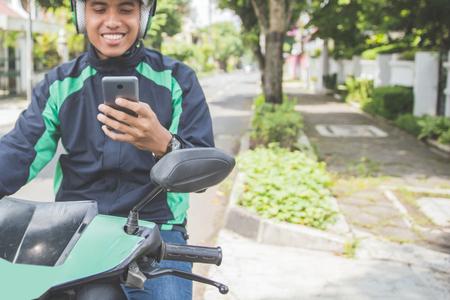 Portret van gelukkige Aziatische man werken als een commerciele motorrijderschauffeur die van zijn smartphone afbestelt