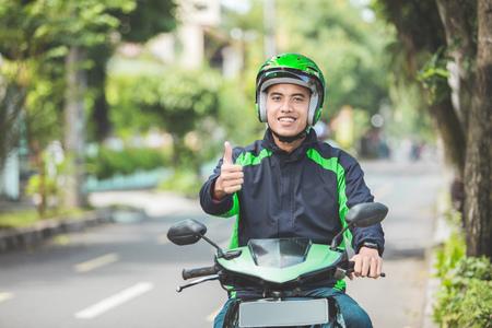 Retrato, feliz, asiático, hombre, trabajo, comercial, motorcyle, conductor, actuación, pulgares ...