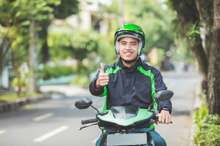 portrait of happy asian man work as a commercial motorcyle driver showing thumbs up to camera