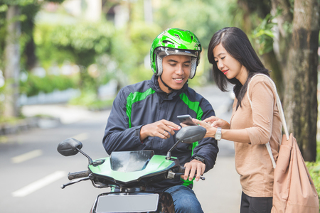 happy young woman standing on sidewalk ordering a commercial motorcycle taxi driver by smartphone