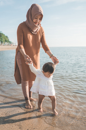 portrait of a mother help her daughter by holding her hand walking on the beach for the first time