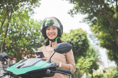 portrait of happy asian woman using mobile phone while riding on motorbike in city street