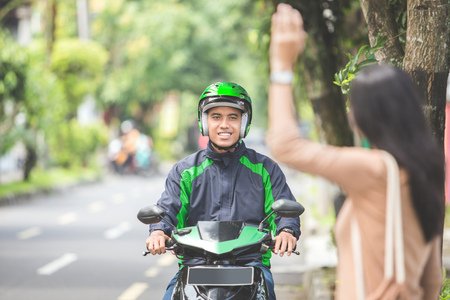 portrait of woman standing on a sidewalk ordering motorcycle taxi by waving her hand photo