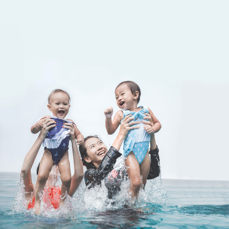 two babies having fun in the swimming pool with their mother photo