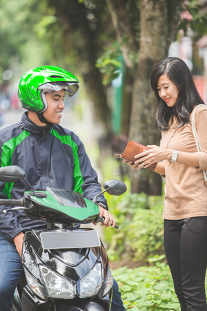 portrait of happy customer pay for her ride to motorcycle taxi driver photo