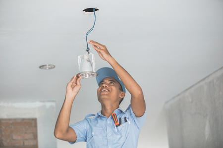 portrait of Electrician wiring a ceiling light Foto de archivo