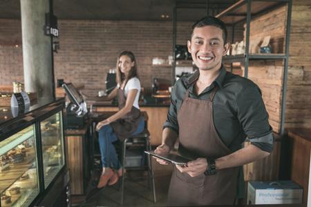 タブレット pc を使用して彼のコーヒー ショップでカフェのオーナー。背景に座っている彼のパートナー