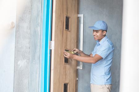 portrait of young asian worker installing doors