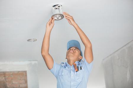 portrait of asian Electrician fitting a ceiling light Reklamní fotografie