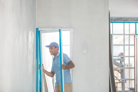 portrait of young asian worker installing doors photo