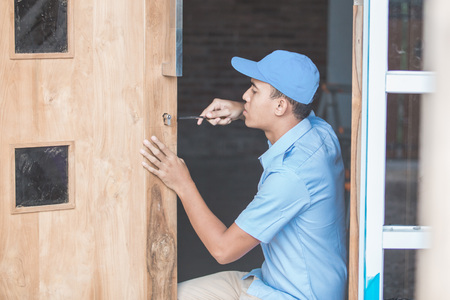 portrait of asian Carpenter Installing Door Lock photo