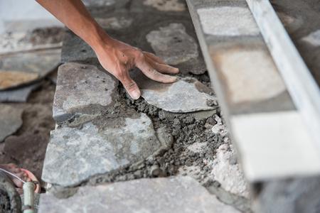 close up of worker installing rock tile or paving