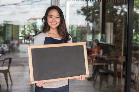 happy small business owner ready to open her cafe for the first time. holding chalk board Archivio Fotografico