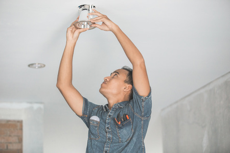 portrait of asian Electrician fitting a ceiling light Imagens