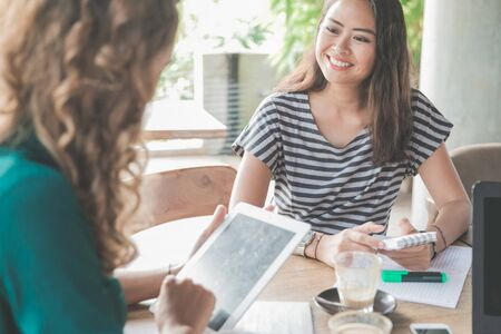 portrait of happy young asian woman talking to her partner on meeting in coffee shop Stock Photo