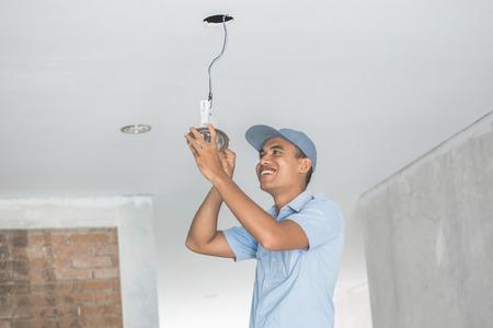 Portret van elektricien bedrading een plafond licht Stockfoto