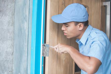 Porträt der jungen asiatischen Arbeiter Türen zu reparieren