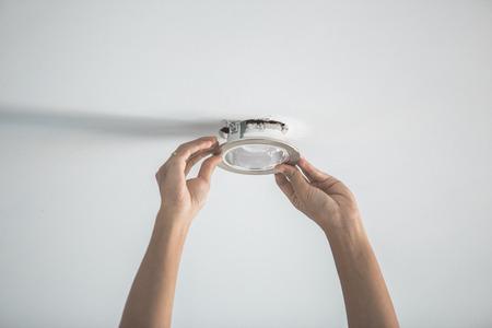 Portret van mannelijke handen installeren contactdoos voor gloeilamp