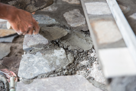 close up of worker installing rock tile or paving