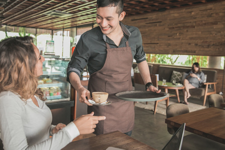 portrait of a male waitress serving coffee to a female customer