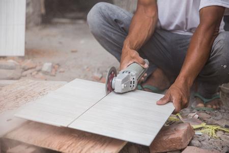 werknemer snijden een tegel met behulp van een haakse slijper op bouwplaats