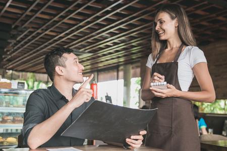 customer ordering food toward waitress at the restaurant photo